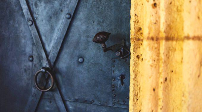 Dunkle, Eiserne Tür Mit Gelb Leuchtender Wand
