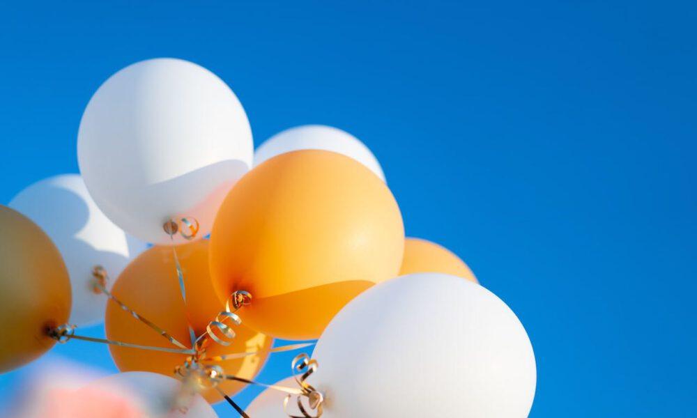 Weiße Und Orangefarbene Luftballons Vor Blauem Himmel