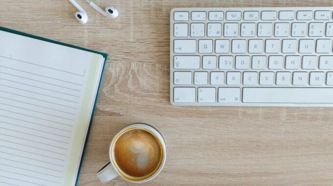 Schreibtisch Mit Kaffee, Tastatur, Notizblock Und Kaffee