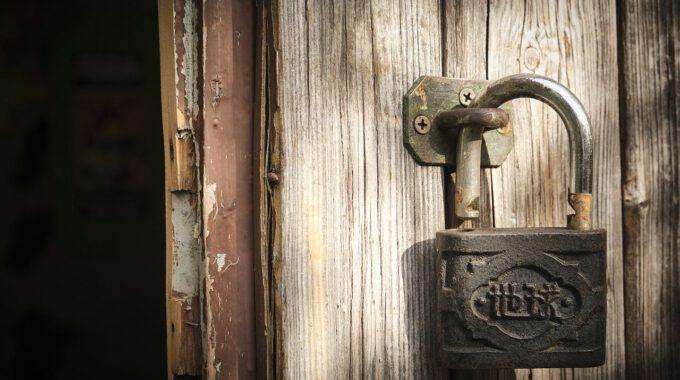 Geöffnetes Vorhängeschloss An Einer Verwitterten Tür