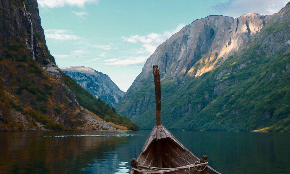 Ein Wikingerschiff Läuft In Einen Fjord Ein - Rechts Und Links Hohe Berge